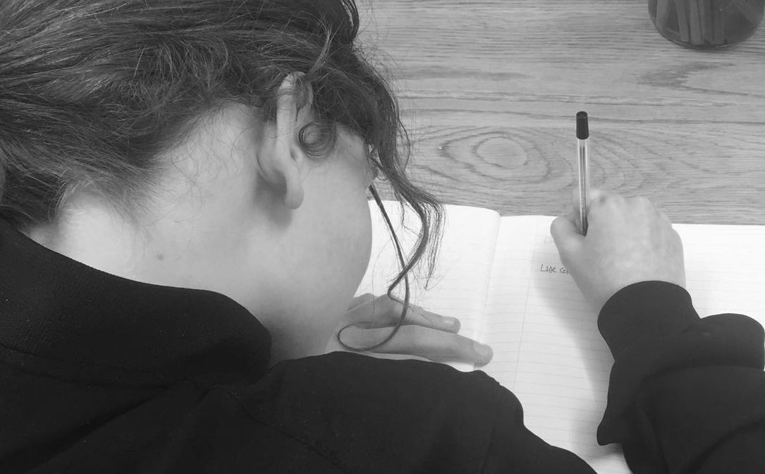 Young girl writing in her notebook
