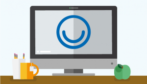 Computer screen with a smiley face on it, sat on a desk with an apple