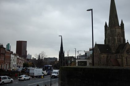 A view of buildings and a church in Leeds, looking very dark and overcast