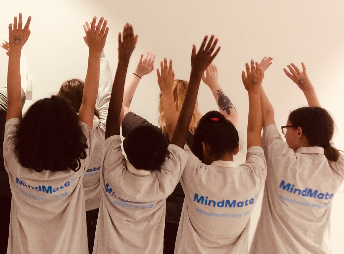 Group of young girls with hands in the air wearing MindMate shirts