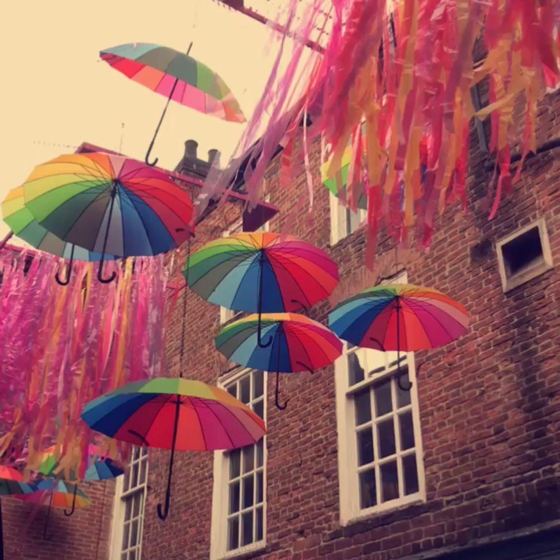 rainbow umbrellas hanging in the street