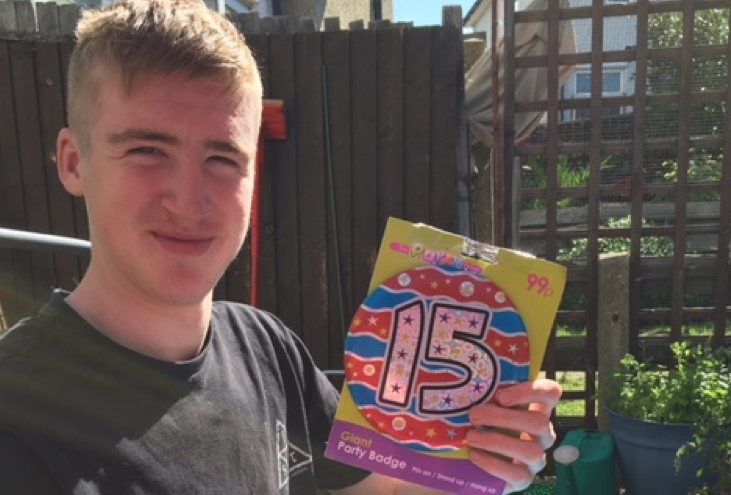 Young man holding a 15 year old birthday badge