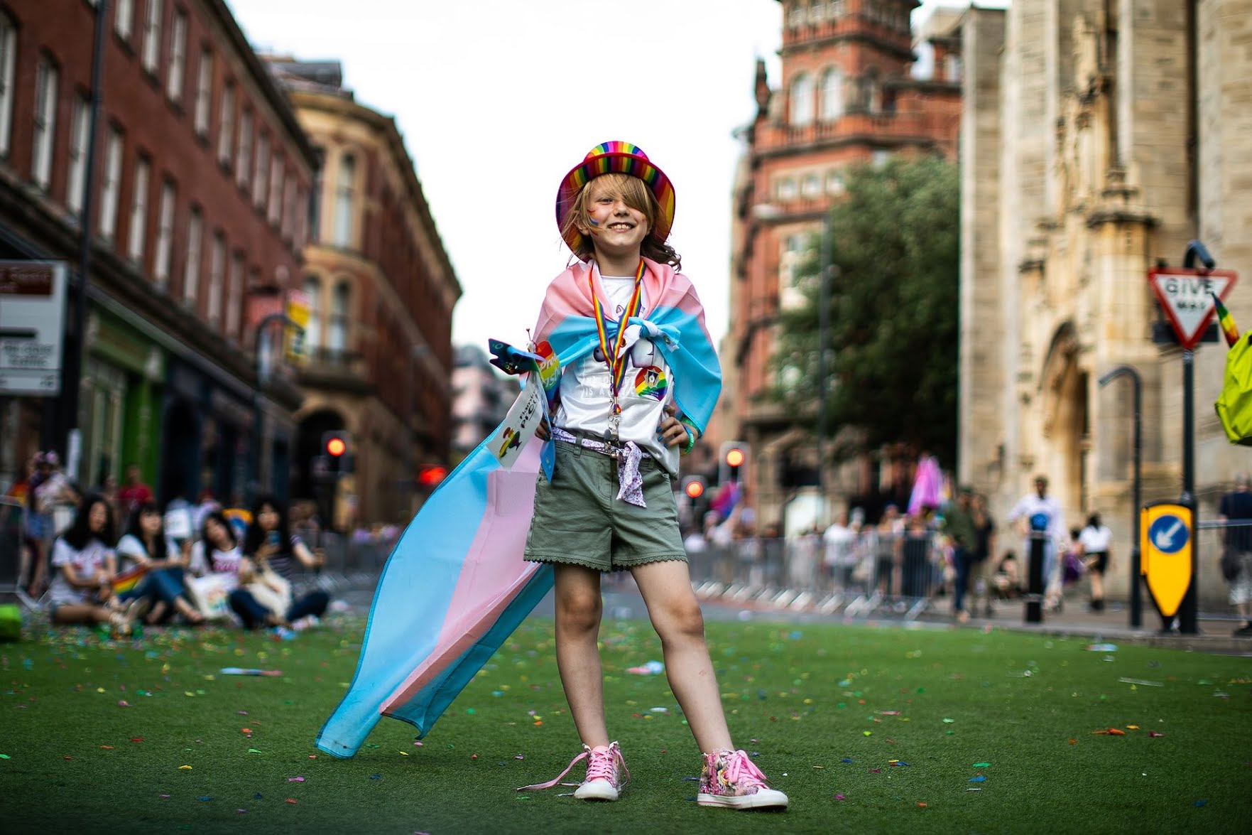 Young person wearing pride flag and hat