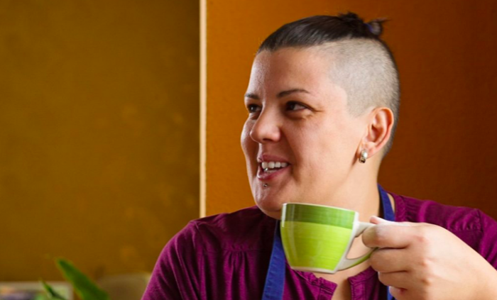 Person smiling while drinking a mug of tea